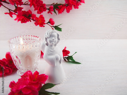 Angel, candle and sakura on a white wooden background - 209664275