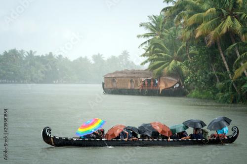 Foto Murales Monsoon time. People crossing a river by boat in rain