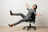 the business woman having fun, falls from chair, dressed in a gray suit poses in front of a white wall - 209691094