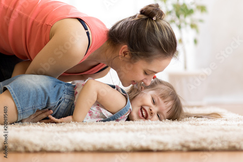 Leinwanddruck Bild Love and family people concept - happy mom and child daughter having a fun at home