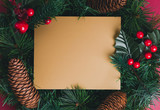 Gold blank greeting card on Green pine christmas wreath with pine cone ,cherry decoration item on red background.Mock up template for adding text or design.Celebration holiday festive concept. - 209697226