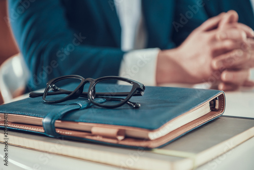 Foto Murales Close up man with glasses and notebooks in office.