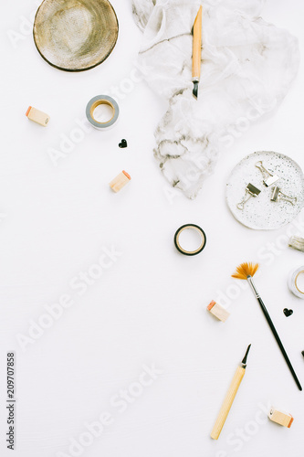 Foto Murales Artist home office desk workspace with paint brushes and tools on white background. Flat lay, top view creative minimal mock up template.