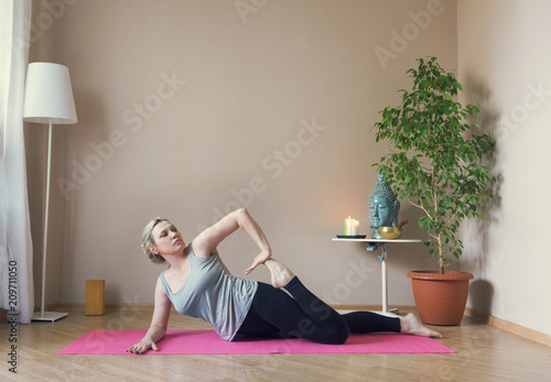 Fototapeta Middle aged woman doing yoga indoors