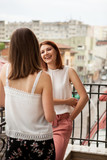 Happy female friends talking and laughing at the balcony of their appartment - 209713275