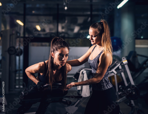 Two beautiful focused fit girls are working out in dark gym together. - 209714619