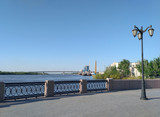 The embankment of Volga River with the art fence and the high lamp and the far port in Astrakhan on the sunny day. The sky is clear. - 209714811