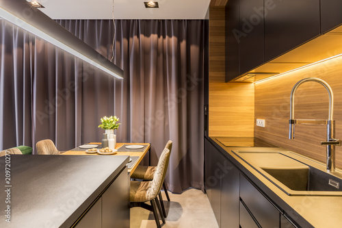 Kitchen interior with dark furniture, dining table with flowers and plates and curtain