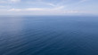 Aerial view of the blue waters of the Mediterranean Sea and specifically of the Tyrrhenian Sea. Sunlight is reflected on the surface of the water. Sky and clouds are on background.