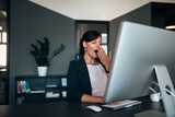 Lovely businesswoman yawning at office desk. - 209727035