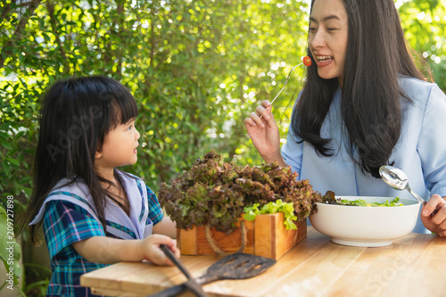 Foto Murales Happy loving family. Mother and her daughter child girl are eating salad in backyard garden. Mother feeding kid vegetables .