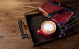 A red cup of latte coffee and old red book on the wooden tray, with statice flowers, topview