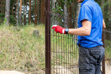 worker installing welded metal mesh fence - 209747602