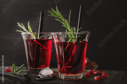 Fresh pomegranate drink with rosemary on black wooden background. Copy space.