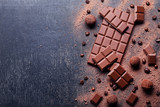 Chocolate pieces with coffee beans and cocoa powder on wooden table - 209759897