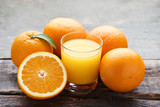 Orange fruit with glass of juice on grey wooden table - 209760069