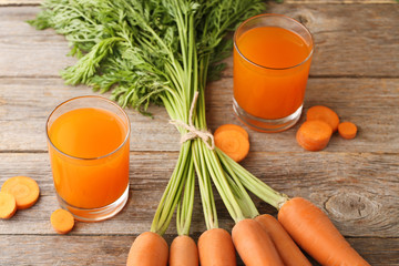 Fresh carrot juice in glasses on wooden table