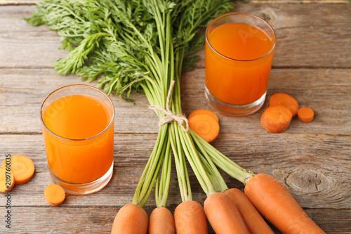 Fototapeta Fresh carrot juice in glasses on wooden table