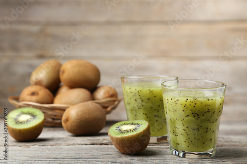 Fresh kiwi smoothie in glass on grey wooden table
