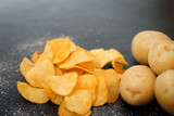 chips recipe. natural food. fried crisps and fresh potatoes on dark background - 209760424