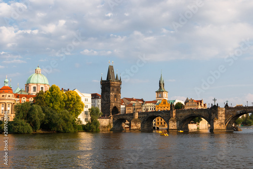 Beautiful and ancient city of Europe - Prague, Czech Republic. View of the city from the observation deck. Small houses and the river Vltava. Charles Bridge and temples.