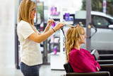 Pretty young woman in beauty salon making hairdress and looking to the mirror.