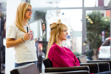 Pretty young hairdresser showing the ready haircut of the female client with mirror in beauty salon. © nenetus