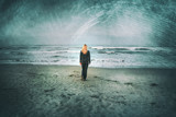 Back view of a sad blonde woman walks alone on sandy beach. Grunge filter effect used. - 209770413