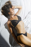 Young sexy woman in black lingerie lying on the bed - 209771622