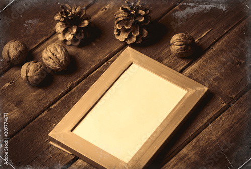 photo of the blue photo frame, nuts and fir-cones on the brown wooden background