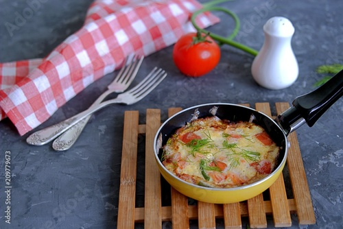 Lush omelette or frittata with garlic arrows and tomatoes in a portioned pan - 209779673