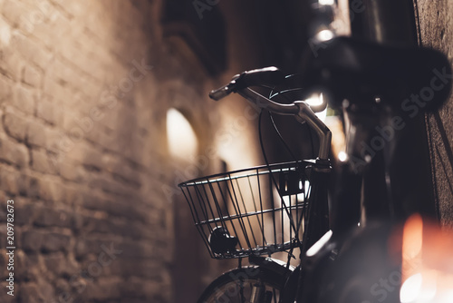 Plexiglas Fiets retro bicycle in the night old city on background bokeh light flare in night architecture, vintage bike in evening street in barcelona town, cycle transportation in backdrop building, travel concept