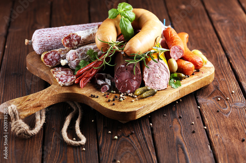 Food tray with delicious salami, ham,  fresh sausages, cucumber and herbs. Meat platter - 209785218