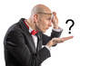Slim bald elegant nerd with glasses and bow tie looking at question mark on his hand with emotion of bewilderment. Isolated on white.