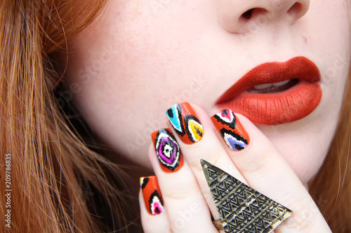 A closeup portrait of a young beautiful redheaded girl with bright natural makeup and colourful nailart.