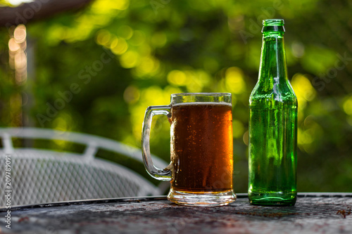 Foto Murales Close up shot of a beer glass and bottle sitting on a table outside with dappled sunlight coming through the background.