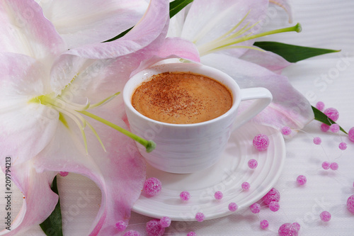 Wall mural Cup of coffee with cinnamon. Coffee in a white cup and lily flowers.