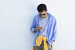 young man with mobile phone to fashion on the blue wall