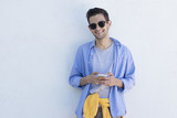 young man with mobile phone to fashion on the blue wall - 209801884