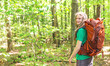 Happy male hiker with backpack trekking through the forest - 209804807