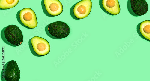 Foto Murales Fresh avocado pattern on a green background flat lay