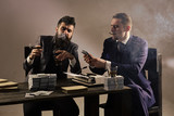 business partnership. Company engaged in illegal business. Men sitting at table with piles of money and typewriter. Businessmen discussing illegal deal while drinking and smoking, grey background. - 209813439