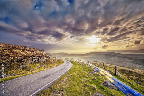Narrow paved road and a sunset in a county Kerry