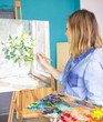 girl artist with a palette of paints draws paintings in an art studio. Palettes and easel, - 209818080