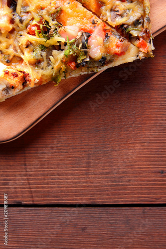 Pizza slices on a wooden board, Italian pizza on a wooden background top view, Italian food in vintage style, appetizing dish for summer vacation, American food, copy space - 209818887
