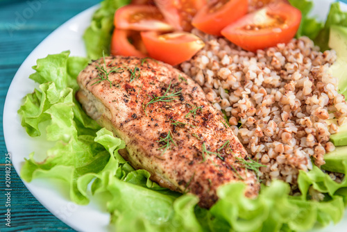 Grilled chicken breast with buckwheat porridge, tomatoes and avocado on blue wooden background. Diet nutrition, healthy food for lunch. - 209823225