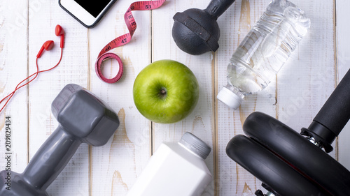 Foto Murales Fitness equipment and Health food on white  wooden background