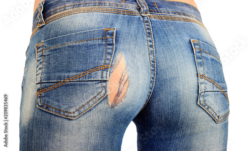 Leinwanddruck Bild blue jeans with a hole in the pope close-up, cracked or torn jeans on the girl. isolated