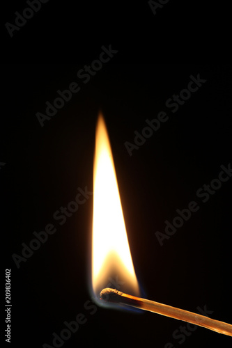Foto Murales ignited match with flame isolated on black background