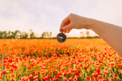 Foto Murales Woman's hand with compass in flower meadow.